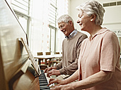 Germany, Cologne, Senior couple playing piano in nursing home - WESTF018704