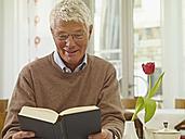 Germany, Cologne, Senior man reading book in nursing home - WESTF018713