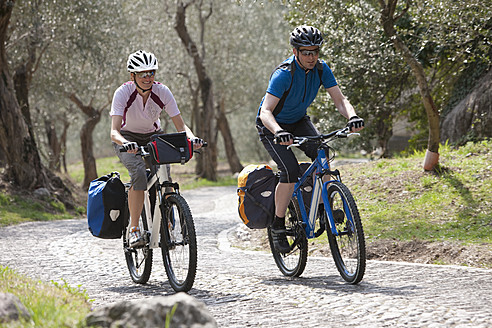 Italy, Trento, Man and woman cycling through country road - DSF000599