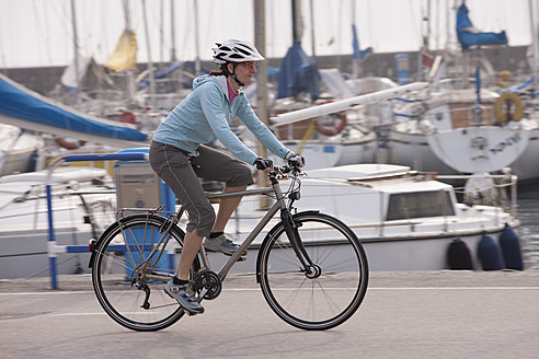 Italy, Trento, Mid adult woman cycling by harbour in Riva - DSF000576