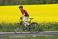 Germany, Bavaria, Starnberg, Mature man cycling through country road - DSF000578