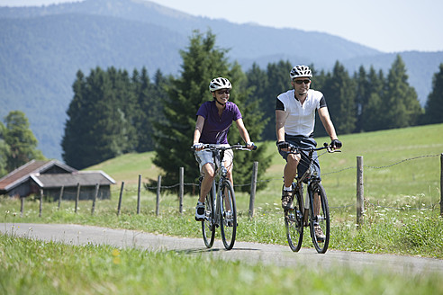 Germany, Bavaria, Man and woman cycling through country road - DSF000581