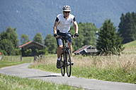 Germany, Bavaria, Young man cycling through country road - DSF000583
