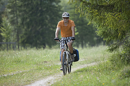 Austria, Tyrol, Young man cycling through single track - DSF000590