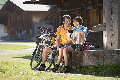 Austria, Tyrol, Man and woman relaxing by bike, smiling - DSF000610