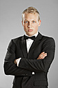 Young man in black suit against gray background - MAEF004656