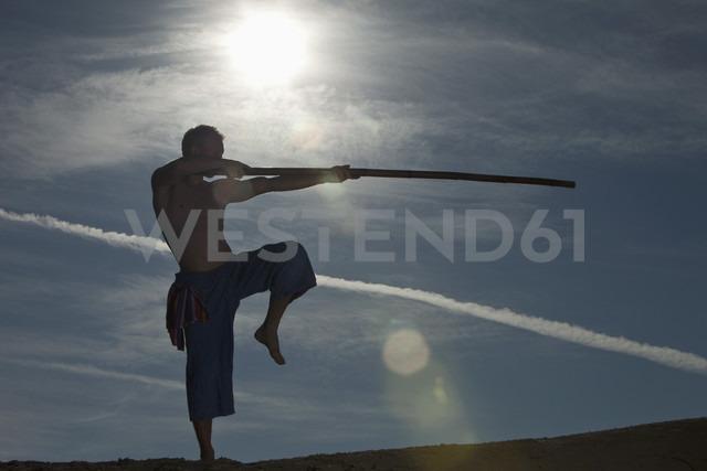 Germany, Bavaria, Young man doing martial arts training with stick - MAEF004675