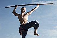 Germany, Bavaria, Young man doing martial arts training with stick - MAEF004666
