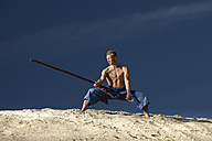 Germany, Bavaria, Young man doing martial arts training with stick - MAEF004667