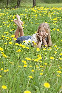 Austria, Teenage girl lying in field of flowers, smiling - WWF002374