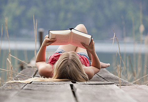 Austria, Teenage girl lying and reading book on jetty - WWF002386