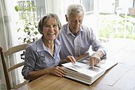 Germany, Bavaria, Senior couple with photo album, smiling - TCF002578