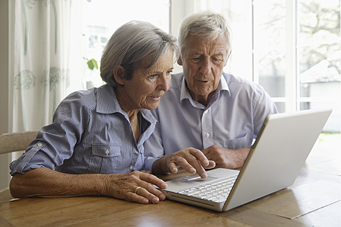 Germany, Bavaria, Senior couple using laptop at home - TCF002591