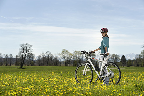 Germany, Bavaria, Mid adult woman riding electric bicycle - RNF000951