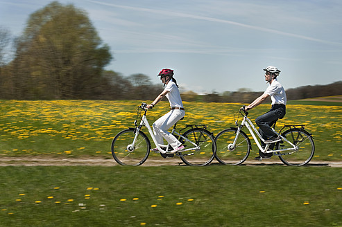 Germany, Bavaria, Man and woman riding electric bicycle - RNF000953