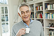Germany, Berlin, Senior man with coffee cup, smiling, portrait - FMKYF000006