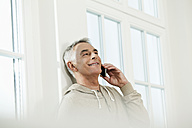 Germany, Berlin, Senior man using cell phone, smiling - FMKYF000018