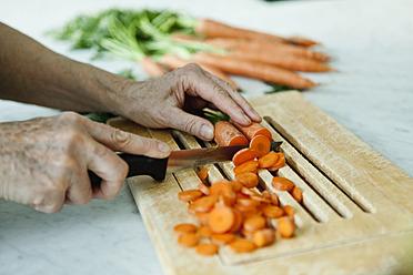 Germany, Berlin, Senior man cutting carrots - FMKYF000030