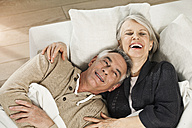 Germany, Berlin, Senior couple lying on couch, smiling - FMKYF000042