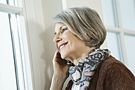Germany, Berlin, Senior woman using cell phone, smiling - FMKYF000069