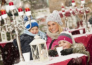 Austria, Salzburg, Mother with children at christmas market, smiling - HHF004197