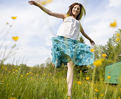 Austria, Young woman running in field of flowers - WWF002425
