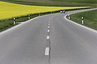 Germany, Bavaria, Car moving on road beside rape field - TCF002680