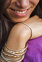 India, Young woman wearing Indian bangles,smiling, close up - MBEF000334