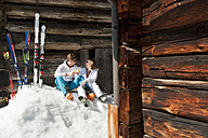 Austria, Salzburg, Young couple sitting in front of alpine hut - HHF004189
