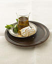 Black tea with fresh peppermint and pastry on plate, close up - KSWF000829