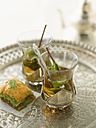 Baklava with peppermint tea on silver tray, close up - KSWF000831