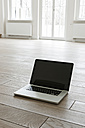 Germany, Berlin, Laptop on wooden floor - FMKYF000081