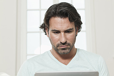 Germany, Berlin, Mature man using laptop - FMKYF000114