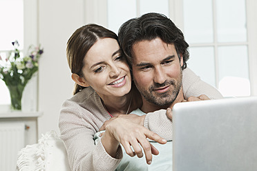 Germany, Berlin, Mature couple using laptop - FMKYF000123