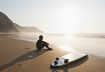 Portugal, Young man sitting on beach by surfboard - MIRF000459
