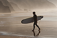 Portugal, Surfer walking on beach - MIRF000468