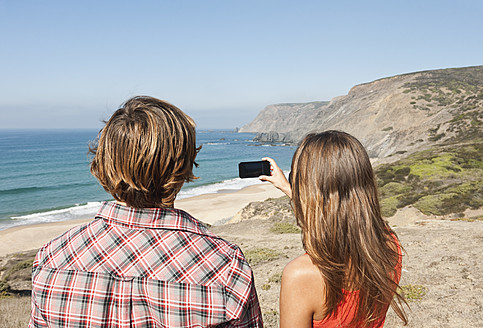 Portugal, Couple taking photograph at beach - MIRF000483