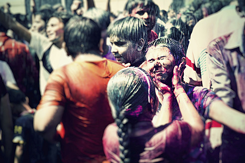 India, Ahmedabad, People colouring each other at Holi festival - MBE000358