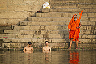 India, Uttar Pradesh, Varanasi, Men taking their morning bath and saying their pujas in Ganges river - MBE000363