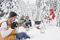 Austria, Salzburg, Men and women sitting at fire place in winter - HHF004211