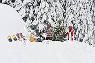 Austria, Salzburg, Men and women sitting by christmas tree in winter - HHF004221