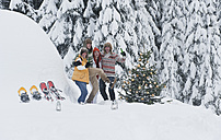 Austria, Salzburg, Men and women dancing by christmas tree in winter - HHF004224