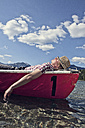 Germany, Bavaria, Mid adult man sleeping in rowing boat - RBF000934