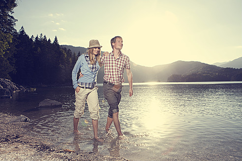 Germany, Bavaria, Couple walking in water, smiling - RBF000942