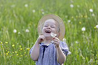 Germany, Bavaria, Girl with dandelion seed, smiling - TCF002750