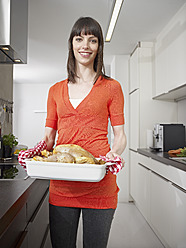 Germany, Cologne, Mid adult woman with roasted chicken, smiling, portrait - RHYF000126