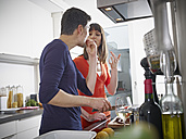 Germany, Cologne, Man and woman cooking together in kitchen - RHYF000132