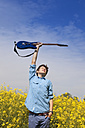Germany, Hamburg, Teenage boy standing in canola field with electric guitar - MSF002679