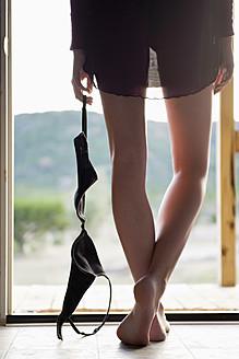 USA, Texas, Young woman holding bra - ABAF000029