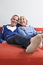 Germany, Leipzig, Senior man and woman relaxing on couch, smiling - WESTF018779